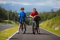 Girl and boy biking Stock Image
