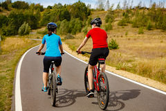 Girl and boy biking Royalty Free Stock Images