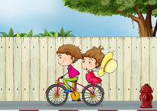 A girl and a boy biking Stock Photo