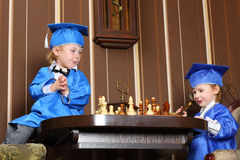 Girl and boy in blue suits play chess Royalty Free Stock Photos