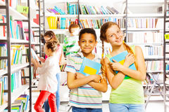 Girl and boy with books together in library Royalty Free Stock Image