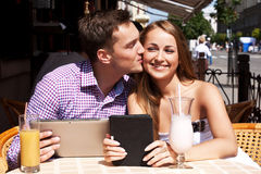 Girl with  boy in  cafe with tablet computer Royalty Free Stock Images