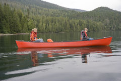 Girl and boy canoeing Royalty Free Stock Image
