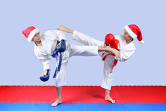 Girl and boy in a cap of Santa Claus are beating leg blows karate Stock Photo