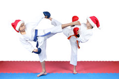 Girl and boy in caps of Santa Claus are beating kick leg Stock Image