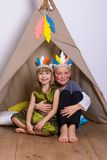 Girl and boy in carnival costumes indians studio. Girl and boy in carnival costumes Indians in the Studio playing and laughing Royalty Free Stock Photos