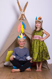 Girl and boy in carnival costumes indians studio. Girl and boy in carnival costumes Indians in the Studio playing and laughing Stock Image