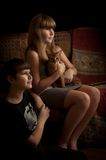 Girl and boy with cat, indoors. Low key. Royalty Free Stock Photography