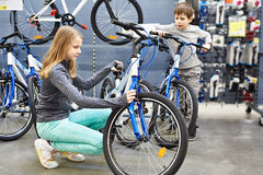 Girl and boy choose bicycle in sports supermarket Stock Photos
