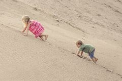 Girl and boy Climbing On The Sand dune. Summer day royalty free stock photography
