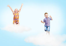 Girl and boy  on clouds and a rainbow Royalty Free Stock Photography