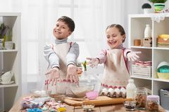 Girl and boy cooking in home kitchen. Children show hands with flour. stock photos