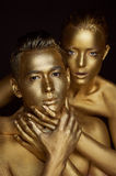 A girl and a boy, covered in gold paint. Large hands on his neck. The lack of freedom. Possessiveness. A girl and a boy, covered in gold paint. Large hands on Stock Image