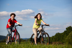 Girl and boy cycling Royalty Free Stock Images