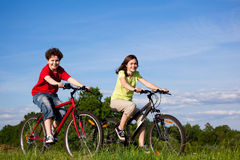 Girl and boy cycling Stock Images