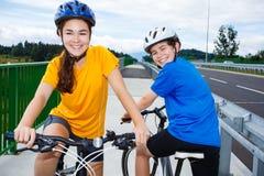 Girl and boy cycling Stock Photos