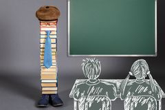 Girl and boy at the desk before unusual teacher and chalkboard. With copy space royalty free stock photos