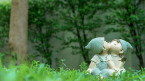 A girl and a boy dolls, kissing and sitting in the garden. A girl and a boy dolls, kissing each other, sitting on the green grass meadow (love concept Royalty Free Stock Image