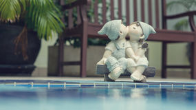 A girl and a boy dolls, kissing and sitting near the pool. A girl and a boy dolls, kissing each other, sitting near the waterl (love concept Royalty Free Stock Photos