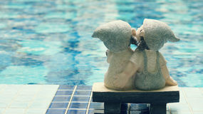 A girl and a boy dolls, kissing and sitting together. A girl and a boy dolls, kissing each other, sitting near the pool (love concept Stock Images