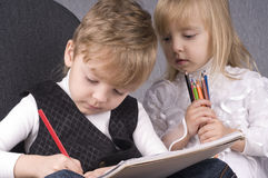 Girl and boy drawing. Beautiful little girl and boy is drawing with crayons on paper Royalty Free Stock Photo