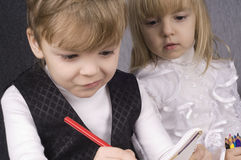 Girl and boy drawing. Beautiful little girl and boy is drawing with crayons on paper Stock Photos