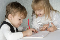 Girl and boy drawing. Beautiful little girl and boy is drawing with crayons on paper Royalty Free Stock Photography