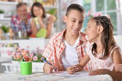 Girl and boy drawing. Little girl and boy drawing with pencils with happy parents on background Stock Photography