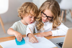 Girl and boy drawing in notebook. Time together. Serious little girl with glasses drawing in the notebook while the little charming boy sitting near her in front Royalty Free Stock Photo