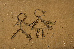 Girl and boy drawn on a beach sand. Royalty Free Stock Image