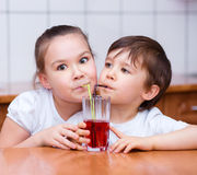 Girl and boy drink juice Royalty Free Stock Photos