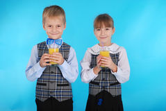 Girl and boy drink juice Stock Photos