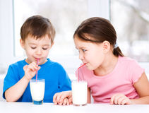 Girl and boy drink tasty fresh milk Stock Photography