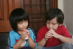 Girl & boy drinking yogurt. Girl and boy sitting on the floor drinking yogurt Royalty Free Stock Image