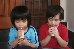 Girl & boy drinking yogurt drinking. Girl and boy sitting on the floor drinking yogurt drink Royalty Free Stock Photo