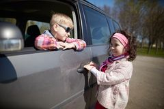 Girl and boy driving fathers car. Little pretty girl and cute boy driving fathers car Stock Images