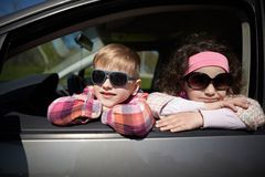 Girl and boy driving fathers car Royalty Free Stock Image