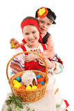 Girl and boy with Easter eggs and a holiday cake. Cheerful children are dressed in Russian national dresses. Girl holds the basket with Easter eggs and a holiday Royalty Free Stock Image