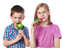 Girl and boy eating a lollipops Royalty Free Stock Images