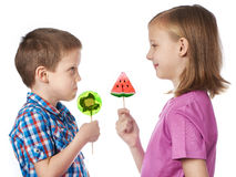 Girl and boy eating a lollipops Royalty Free Stock Image