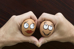 Girl and boy egg face in man hand Royalty Free Stock Photo