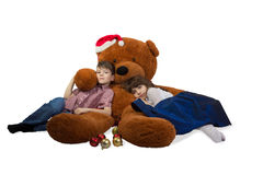 Girl and boy are embracing huge teddy bear with Santa`s hat on his head. Stock Photos