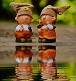 Girl and Boy Figurines Facing Each Other Near Body of Water Royalty Free Stock Image