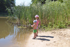 A girl and a boy fishing. A sister and brother, with fishing rods, outdoors, summer, Sunny Stock Photos