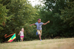 Girl and boy flying a kite Stock Images