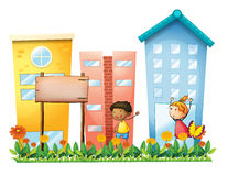 A girl and a boy in the garden with a wooden signboard Royalty Free Stock Images