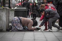 Children helping a beggar lady. A girl and a boy giving some morning to a lady who is begging on the street of Brussels Stock Photos