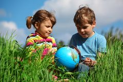 Girl and boy with globe on meadow Royalty Free Stock Images