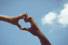Girl and boy hand in heart form love blue sky Stock Photography