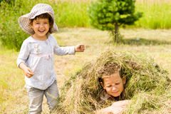 Girl and boy and hay. Two kids playing with hay Royalty Free Stock Photography